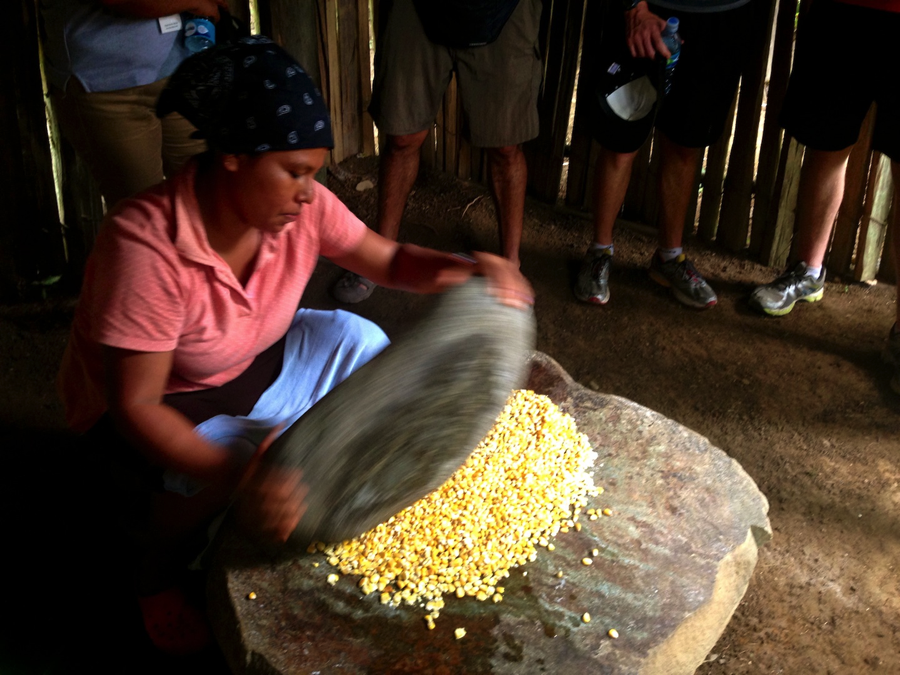 Bribri woman grinding maize the traditional way