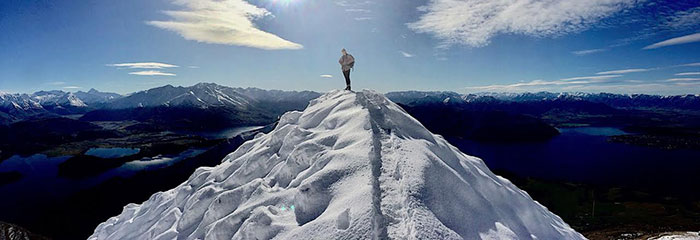 Oxy student Annika Smith standing at the summit of Roy's Peak in New Zealand