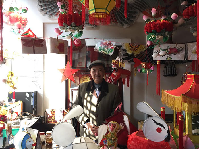 Man surrounded by handmade Chinese lanterns