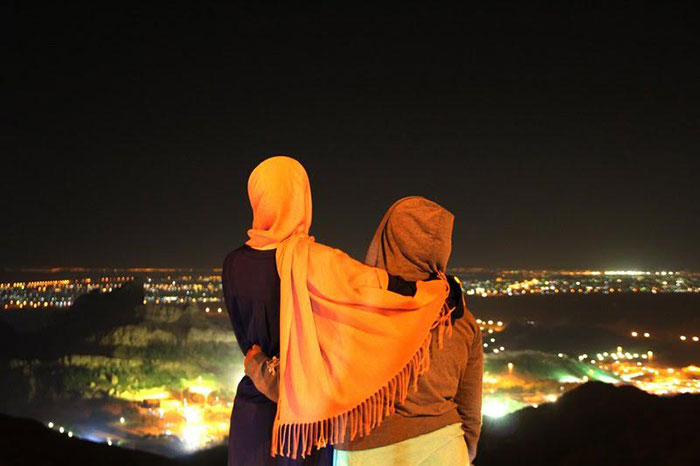 Two women looking over the night landscape of Al Ain