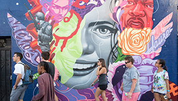 Students walk in front of a colorful street mural in Los Angeles