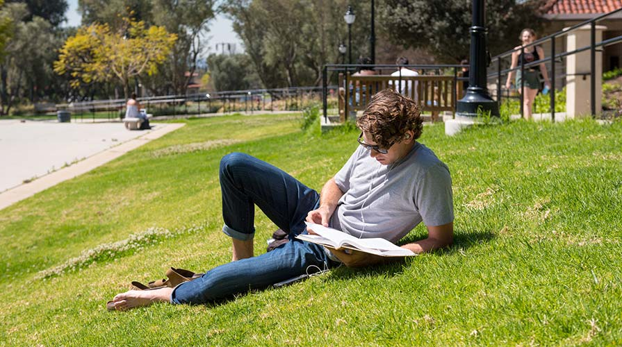Student lounging on the campus lawn reading a book