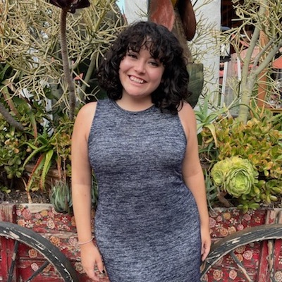 Mia Villegas, a young woman in a gray dress, smiles in front of a cart of desert plants.