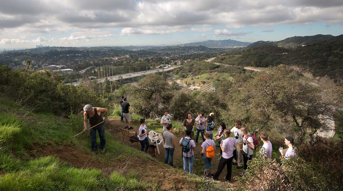 Oxy student volunteers work in a garden overlooking East LA
