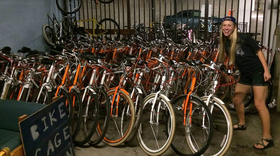 Oxy student poses next to a fleet of rentable bicycles