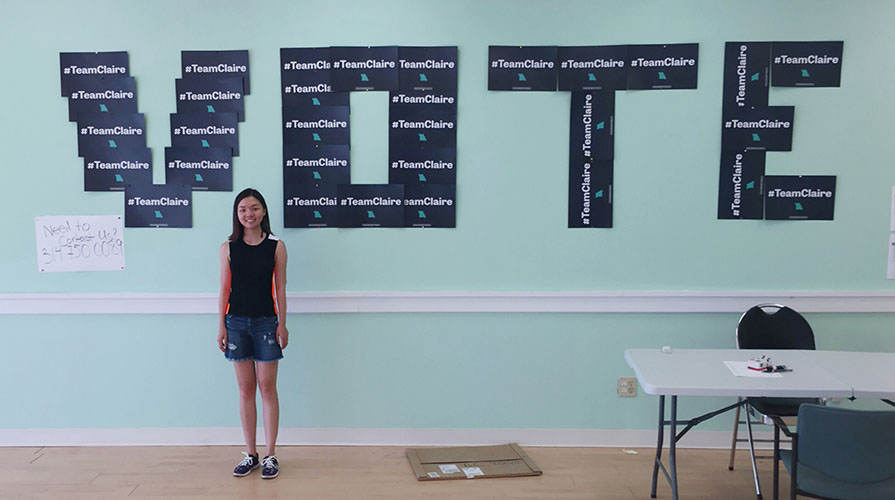 Student stands in front of wall decorated with campaign signs