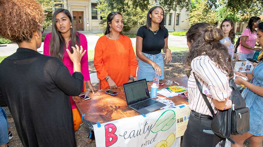 Students at a booth talking to visitors at the Involvement Fair