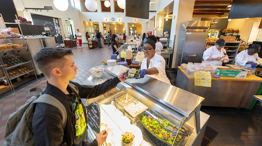 A student accepts a plate at the dining hall salad bar