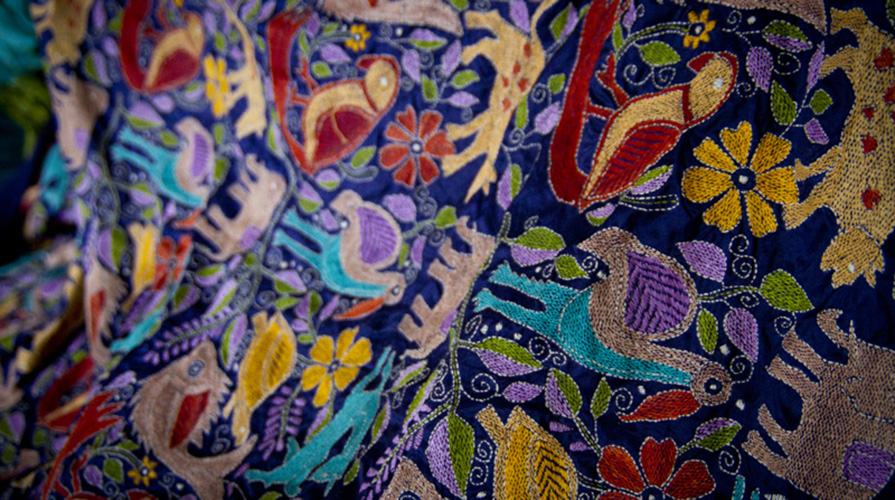 A colorful tapestry embroidered with elephants and other animals