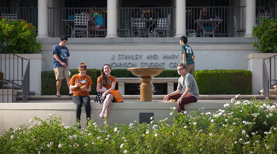 Students sit in front of Johnson Student Center