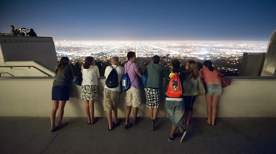Students look over the lights of Los Angeles at night from the Griffith Park Observatory