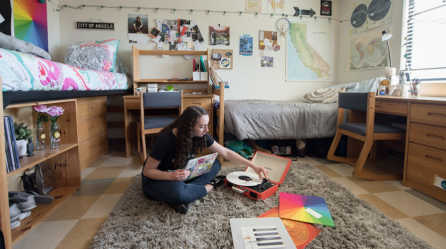 A student sits on the floor of her dorm room with a record player and a colorful selection of records