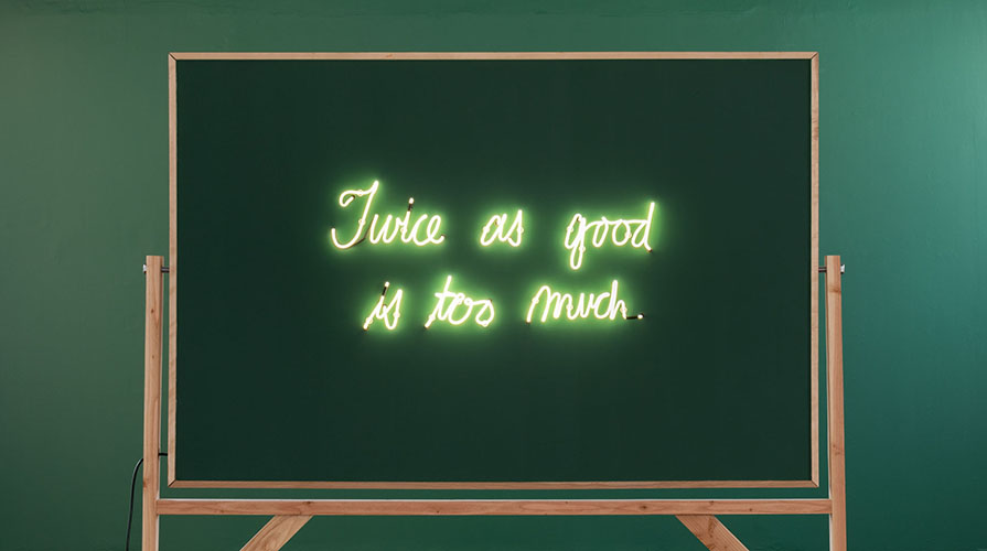 """A blackboard with glowing letters that read """"Twice as good is too much."""""""