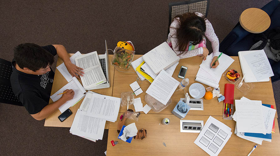 Two students study at a table surrounded by papers and notebooks