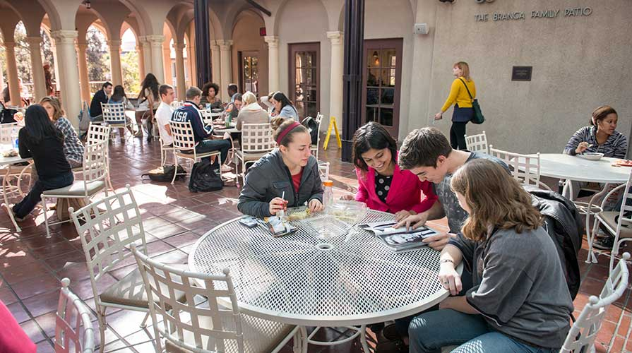 Students sitting together at a table on Branca Patio