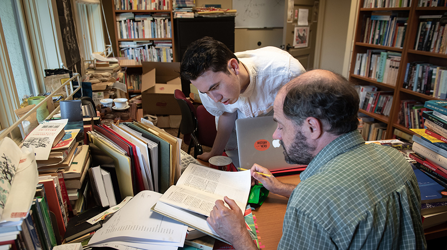 Oxy student Kevin Conroy leans attentively over a desk held by Professor Alexander Day in an office filled with books