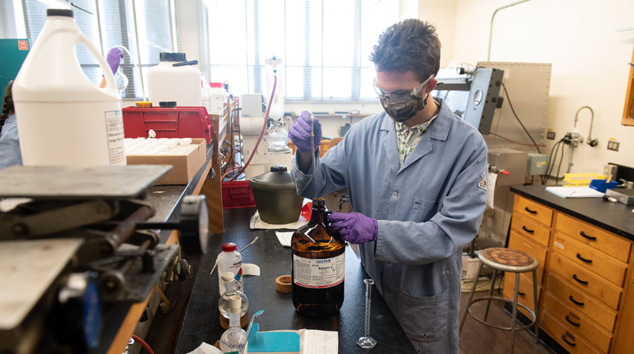 A student wearing a lab coat, gloves, and mask holds a beaker in a science lab