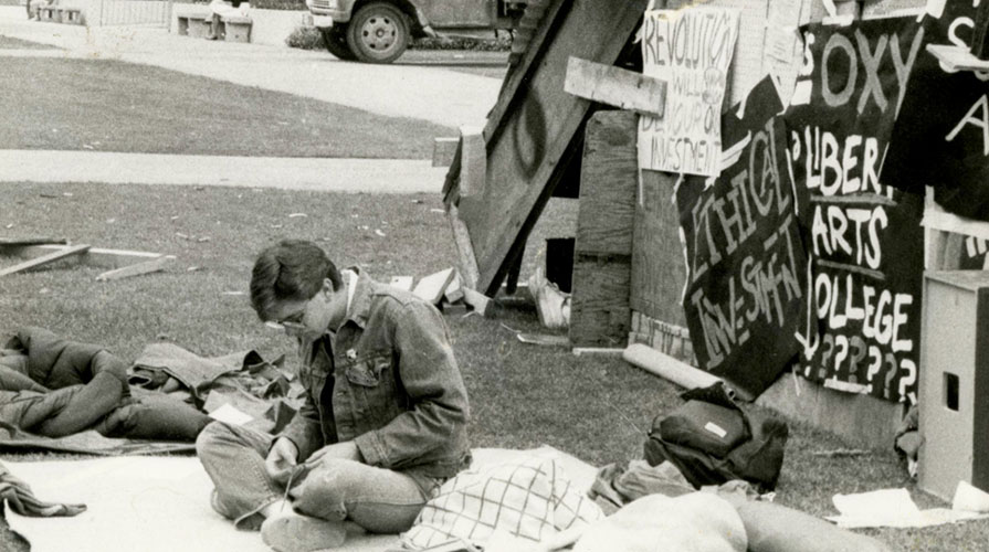 A black and white photo of an Oxy student sitting in protest with a number of signs in the background