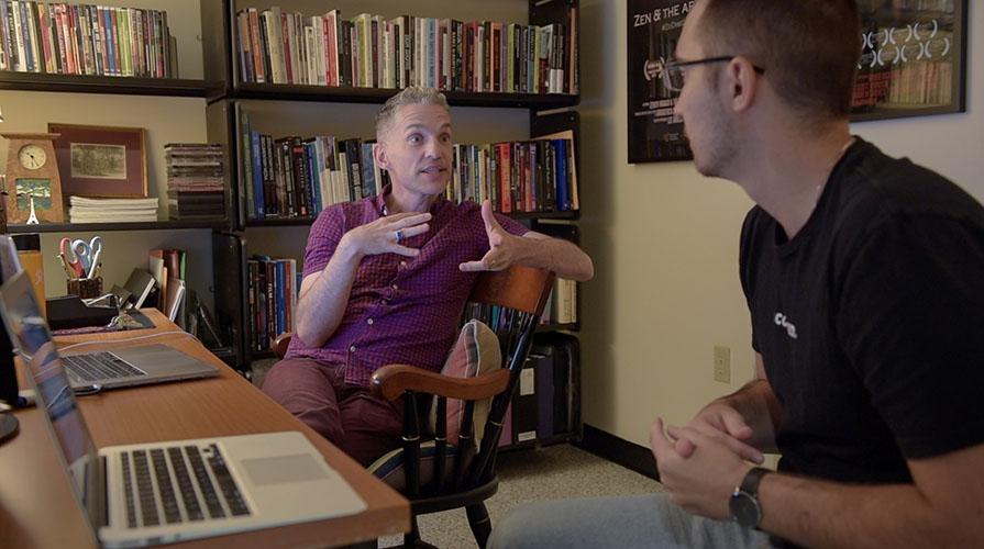 Faculty member Broderick Fox speaks to student Brendan Galbreath in an office full of books