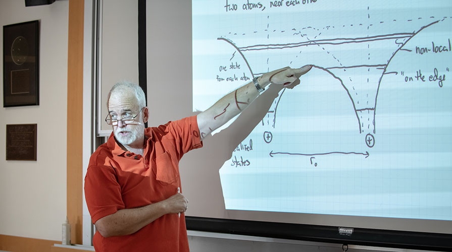 Professor George Schmeideshoff stands in front of a projections of a physics diagram while teaching class