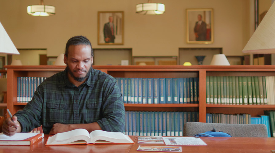 Cameron Peters '18 studying in the library