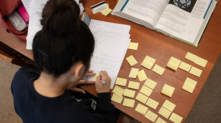 A student studies for final exams at a desk covered with papers and sticky notes