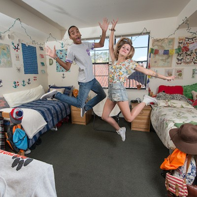 Two students jump into the air in their decorated dorm room