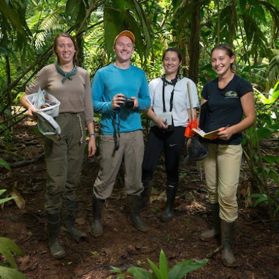 Students in Costa Rica pose in jungle with cameras and data collection materials