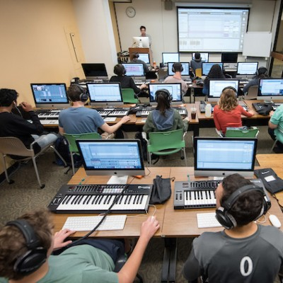 Music production students use electronic keyboards and computers in classroom