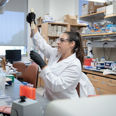 Young woman in lab coat and safety goggles uses pipette filled with blue liquid