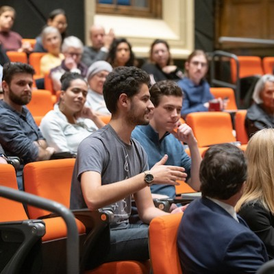 Student of color speaks in audience while others look on
