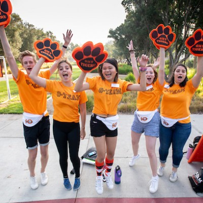 Oxy students in orange T-shirts and tiger paws shout and celebrate