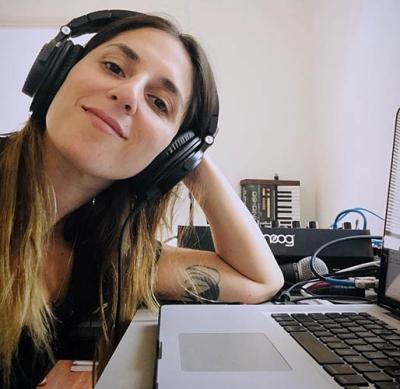 Professor Ramona Gonzalez ssitting at her desk making music