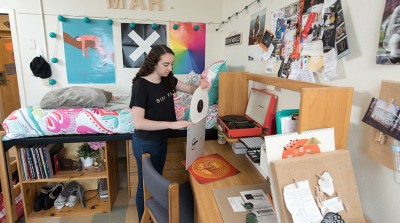 Student in residence hall places vinyl record back into its sleeve, in front of their raised bed and band posters.