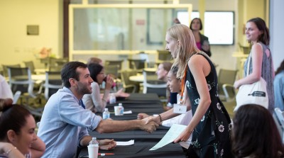 A student shakes the hand of a prospective employer for Oxy's InternLA program