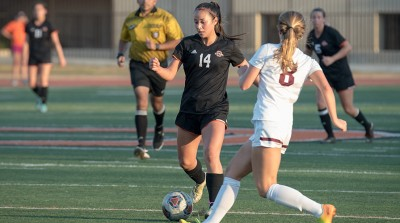 Student wearing black uniform kicks soccer ball while her opponent runs to meet her