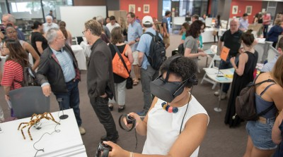 One student uses a VR headset while students and professors chat in the background at Oxy's Academic Fair
