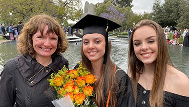 Oxy parent and sibling flank graduating Oxy student wearing graduation cap, with Gilman Fountain in background