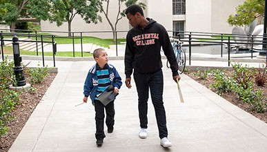 oxy student walking with a young child