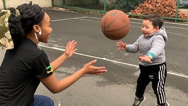 Student Darla Howell plays basketball with a Chinese toddler