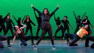Student dancers perform at Dance Pro, with arms upraised in front of green background.