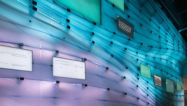 The media wall in Johnson Hall glows blue, turquoise, and purple
