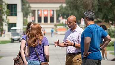 Students and faculty talk in the Academic Quad with Thorne Hall in the background