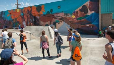 Students look towards where a faculty member is pointing, towards a mural with people of color featured