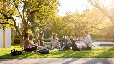 A group of students sit chatting in a circle on the quad at sunset