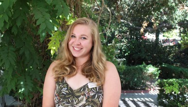 Haley smiles in patterned tank top and name tag with a background of foliage