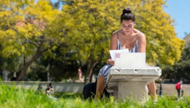A student studies on the academic quad