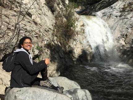 Roshni Katrak-Adefowora sitting in front of a waterfall