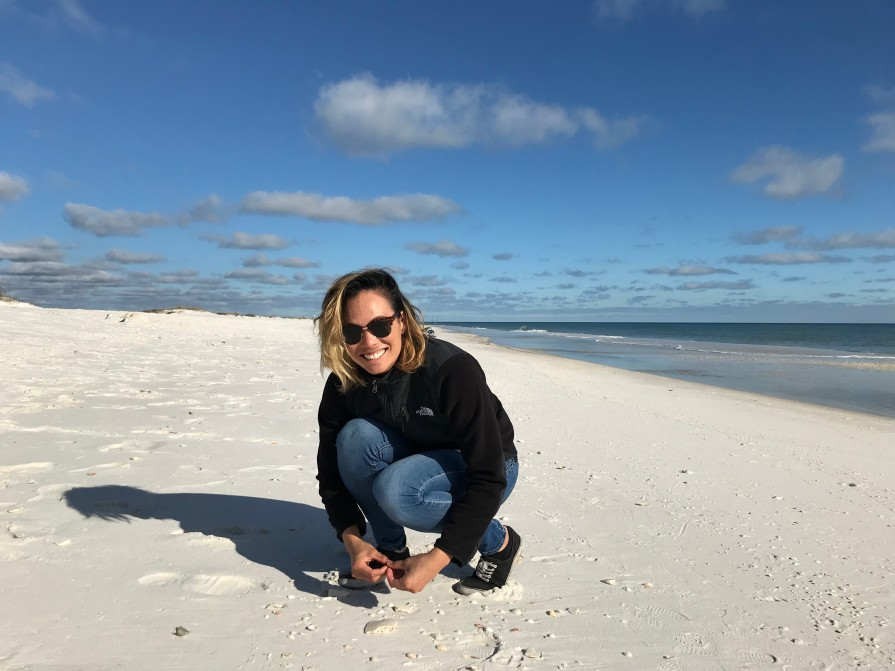 Dr. Caitlin Fong crouching on a beach