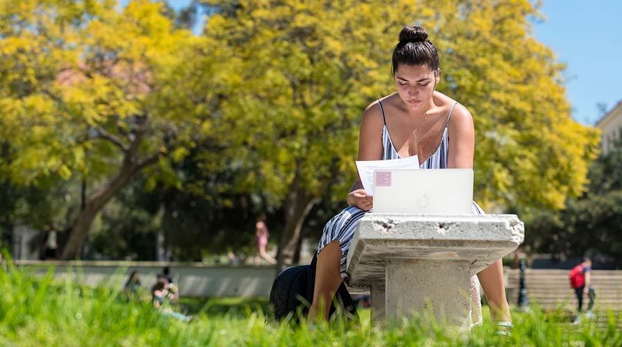 A student studies on the academic quad